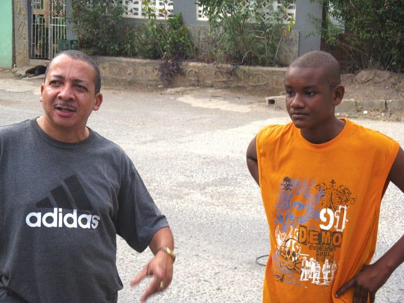 El Diácono Baldwin Powell (izquierda) y un joven residente de Jamaica les cuentan a los visi- tantes sobre su nación isleña caribeña.( Cortesía de Maryknoll Church Engagement DIvision/Jamaica)