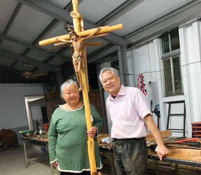 Una mujer local y el padre Nguyen están jun- to a una cruz hecha por el misionero a pedido de un sacerdote vietnamita enTaiwán. (Cortesía de Nhuan Nguyen/Taiwán)