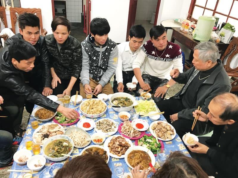 Trabajadores migrantes vietnamitas comparten una comida con el padre Nguyen después de la misa, en la época en que el sacerdote trabajaba para reconstruir la parroquia. (Cortesía de John y Justine Chu/Taiwán)