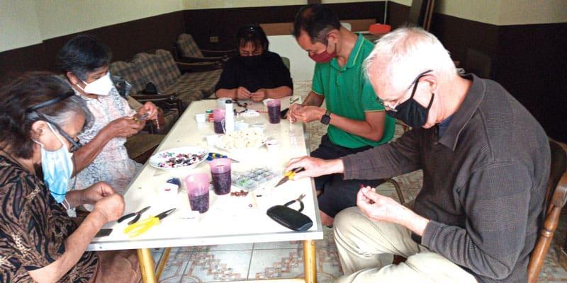 Durante la pandemia del COVID-19, los integrantes de las comunidades cristianas se reunieron con el padre Masson y el seminarista Matthew Sim (camisa verde) para hacer rosarios. (Rossy Bedoya/Bolivia)