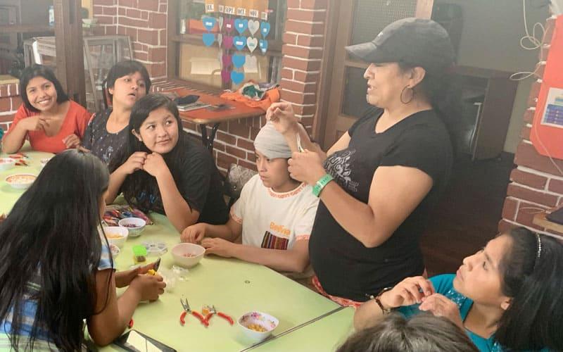 Rossy Bedoya (con gorra negra) visita a niñas en el refugio Our Home que fueron víctimas de abuso y les enseña a hacer rosarios. (Matthew Sim / Bolivia)