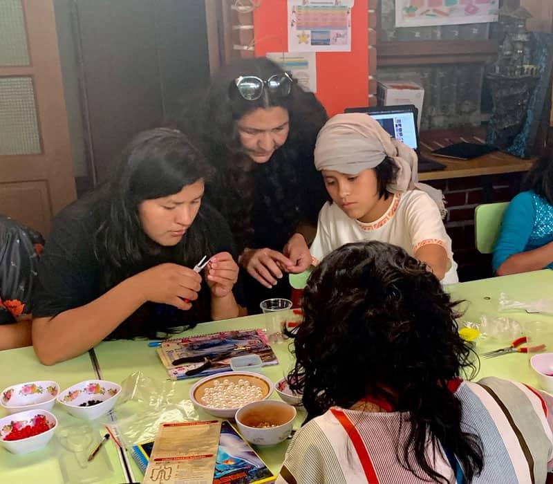 Lorena Simons (centro) enseña a las niñas en el refugio Our Home en Cochabamba, Bolivia, a hacer rosarios. (Matthew Sim / Bolivia)