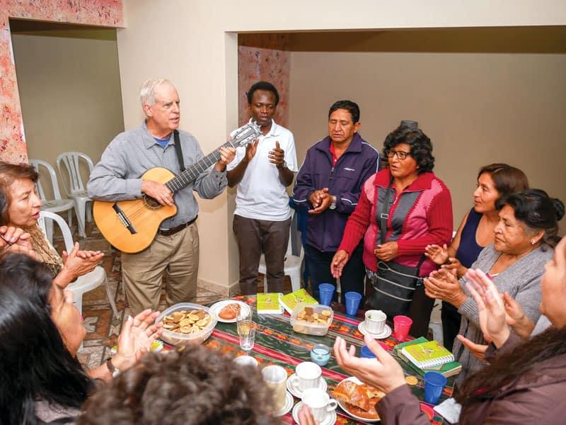 El padre Masson, tocando la guitarra, y el seminarista Maryknoll John Siyumbu (polo blanco) se reunieron con las comunidades cristianas en la casa del padre Masson en Cochabamba. (Nile Sprague/Bolivia)