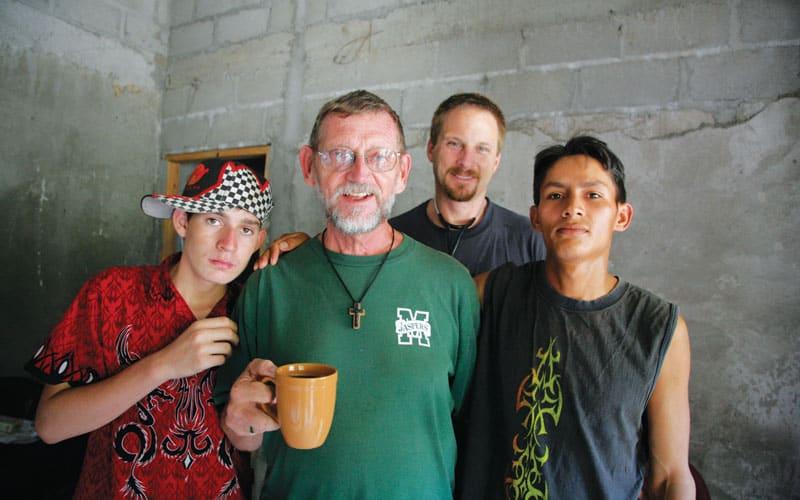 El Padre Maryknoll Thomas Goekler toma un descanso para beber un café con dos jóvenes locales y un médico visitante, Brandon Stark de Chico, California, en una foto de 2006. (Sean Sprague/Honduras)
