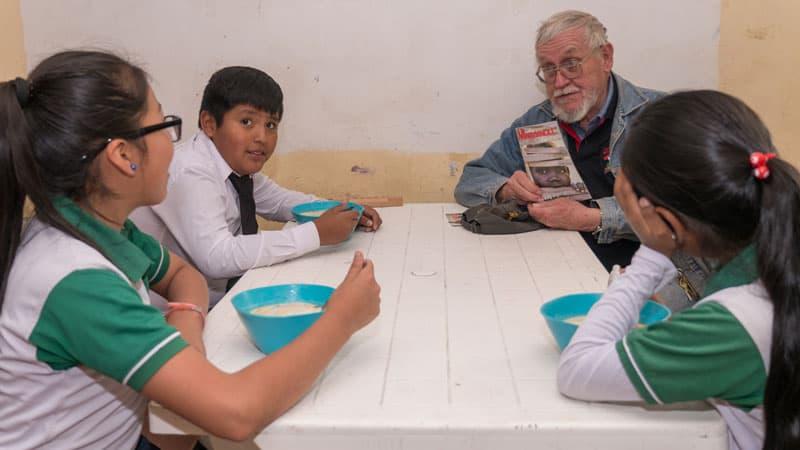 Tutoría escolar en medio de la pandemia: En un almuerzo, antes de COVID-19, el padre Paul Sykora muestra la revista Maryknoll a estudiantes que asisten al programa de tutoría escolar en Nueva Vera Cruz, Cochabamba, Bolivia. (Nile Sprague/Bolivia)