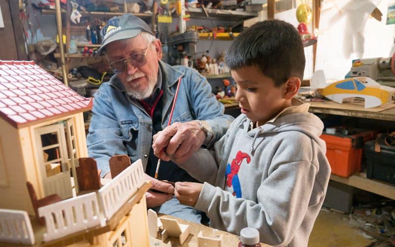 Tutoría escolar en medio de la pandemia: El padre Sykora, quien dirigeel programa de tutoría escolar para nños en Cochabamba, Bolivia, le enseña a un niño como pintar una casa de juguete, antes de la pandemia. (Nile Sprague/Bolivia)