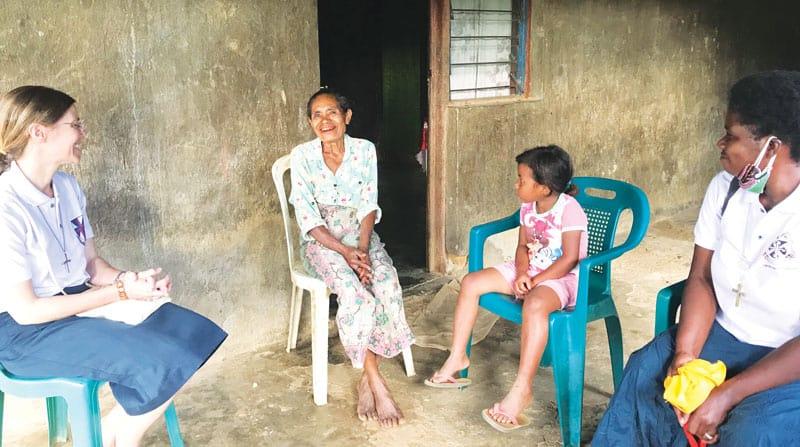 Las hermanas Maryknoll Julia Shideler (izquierda) y Susan Wanzagi (derecha con mascarilla) visitan hogares y escuchan las preocupaciones de sus vecinos en el distrito de Aileu. (Cortesía de Susan Wanzagi/Timor Oriental)