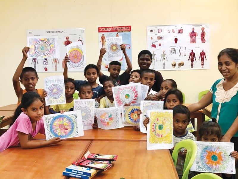 La misionera Maryknoll Susan Wanzagi sonríe al fondo mientras los niños a los que ella enseña muestran sus obras de arte. Además enseña inglés a niños, jóvenes y profesionales en Timor Oriental. (Cortesía de Susan Wanzagi/Timor Oriental)