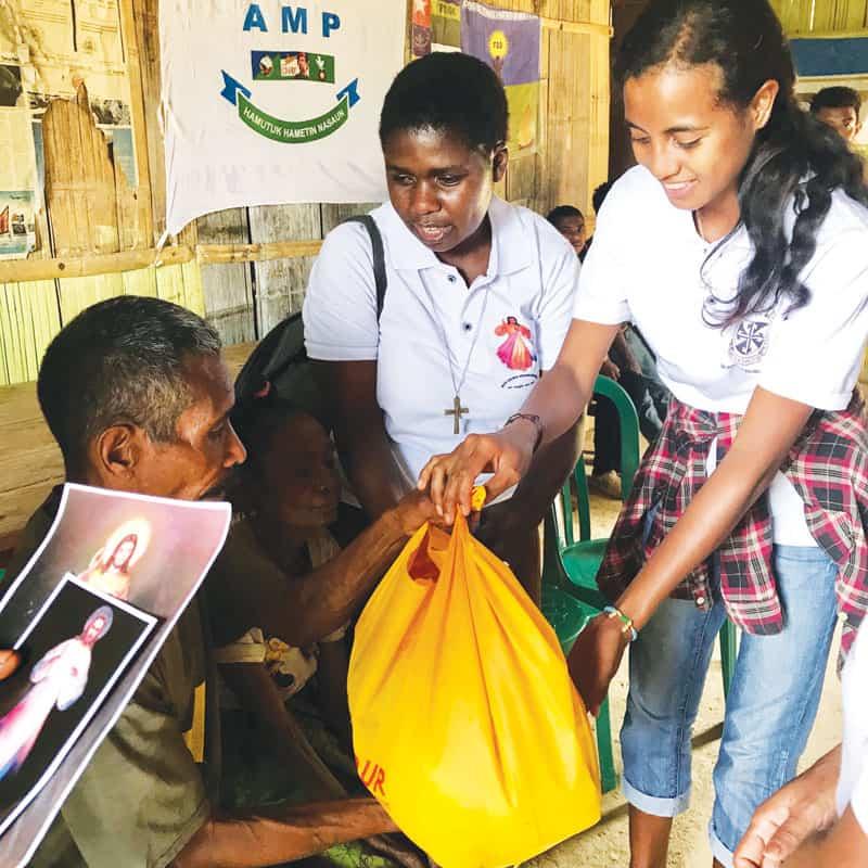 La hermana Wanzagi y el grupo de voluntarios de la Divina Misericordia visitan a un vecino anciano. (Cortesía de Susan Wanzagi/Timor Oriental)