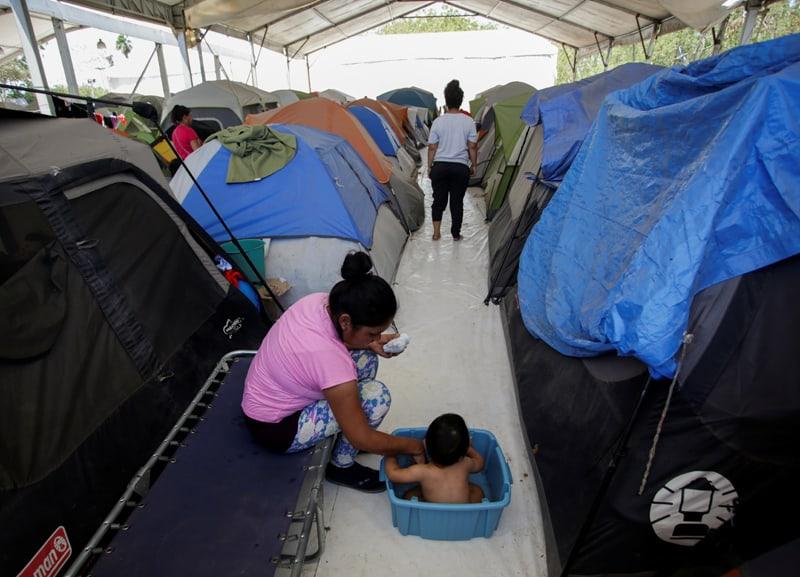 Una mujer migrante baÒa a su hijo fuera de su tienda de campaÒa en un campamento de migrantes en Matamoros, MÈxico, el 30 de abril de 2020. Personas buscando asilo en Estados Unidos contin˙an viviendo en el campamento pero muchos han dicho que tienen miedo de seguir allÌ por todos los percances y la amenaza de la violencia a manos de carteles que controlan la frontera. (Foto CNS/Daniel Becerril, Reuters)