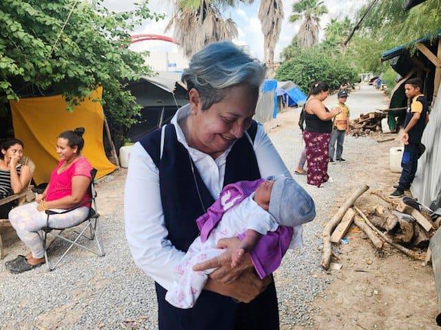 La hermana Norma Pimentel, directora ejecutiva de Caridades Católicas del Valle del Río Grande, aparece en una foto sin fecha sosteniendo a su ahijado en el campamento de migrantes en Matamoros, México, durante la pandemia de COVID-19. El nacimiento del bebé, como la mayoría de los partos en el campamento, representó un riesgo para la madre y el bebé, ya que la atención médica no es un hecho. (Foto del CNS / cortesía de la hermana Norma Pimentel)
