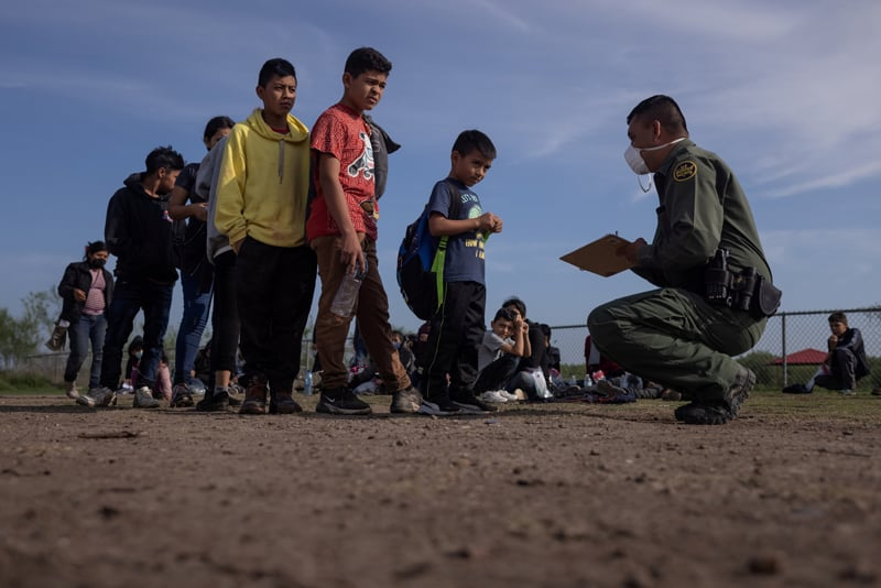 Anderson, a 6-year-old unaccompanied minor from El Salvador, stands in line with other asylum-seeking children in La Joya, Texas, May 14, 2021, as they identify themselves to a Border Patrol agent after crossing the Rio Grande from Mexico. (CNS photo/Adrees Latif, Reuters)