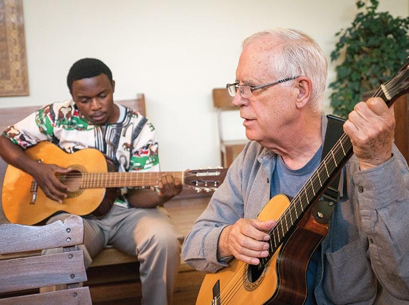 El Padre Maryknoll Paul Masson, guía espiritual de los candidatos Maryknoll en Bolivia, acompaña a tocar la guitarra a Mutende en una misa celebrada en la capilla de Maryknoll. (Nile Sprague/Bolivia)