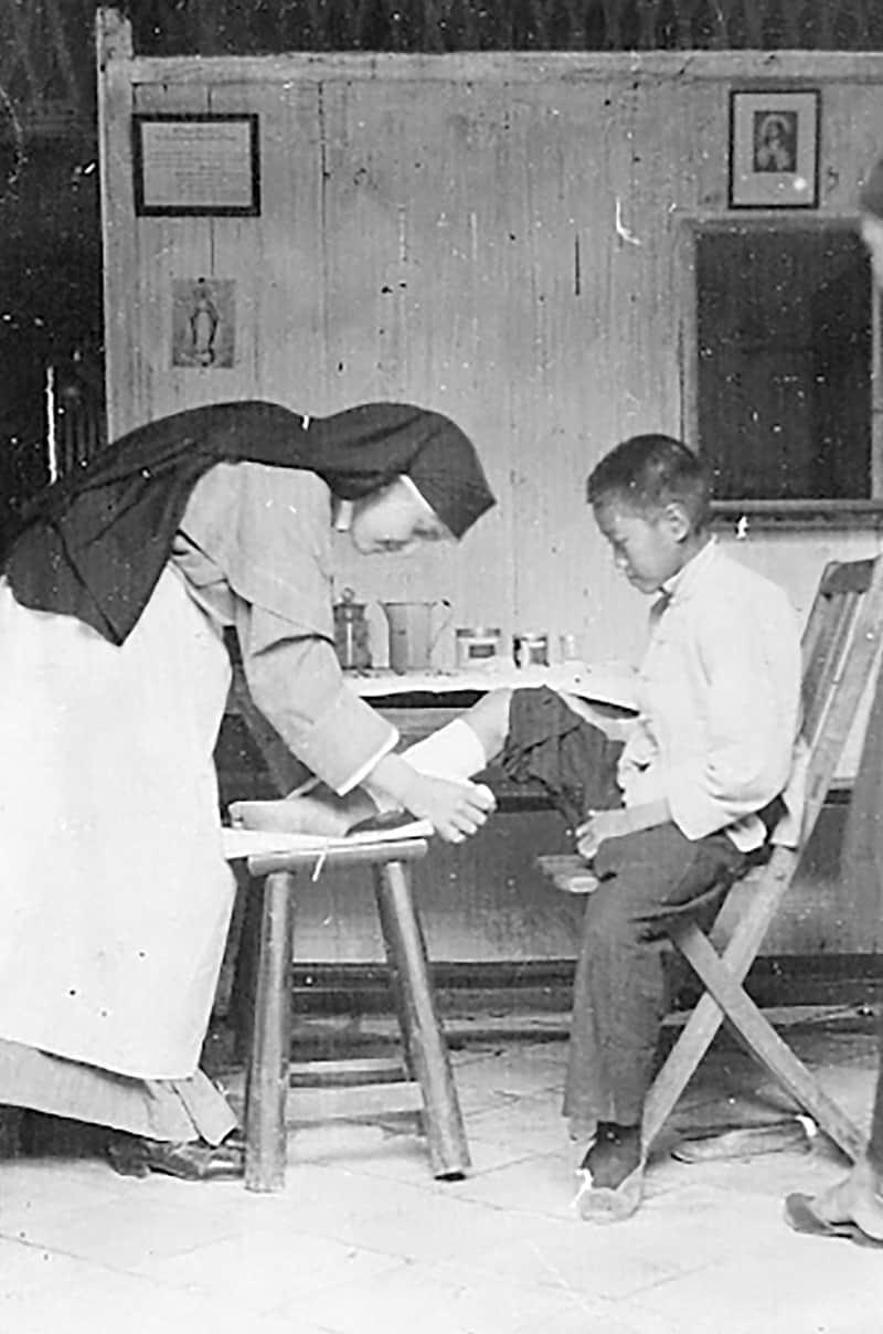 La Hermana Marie de Lourdes Bourguignon, enfermera titulada, le venda el pie a un joven paciente en Yeungkong en 1923.