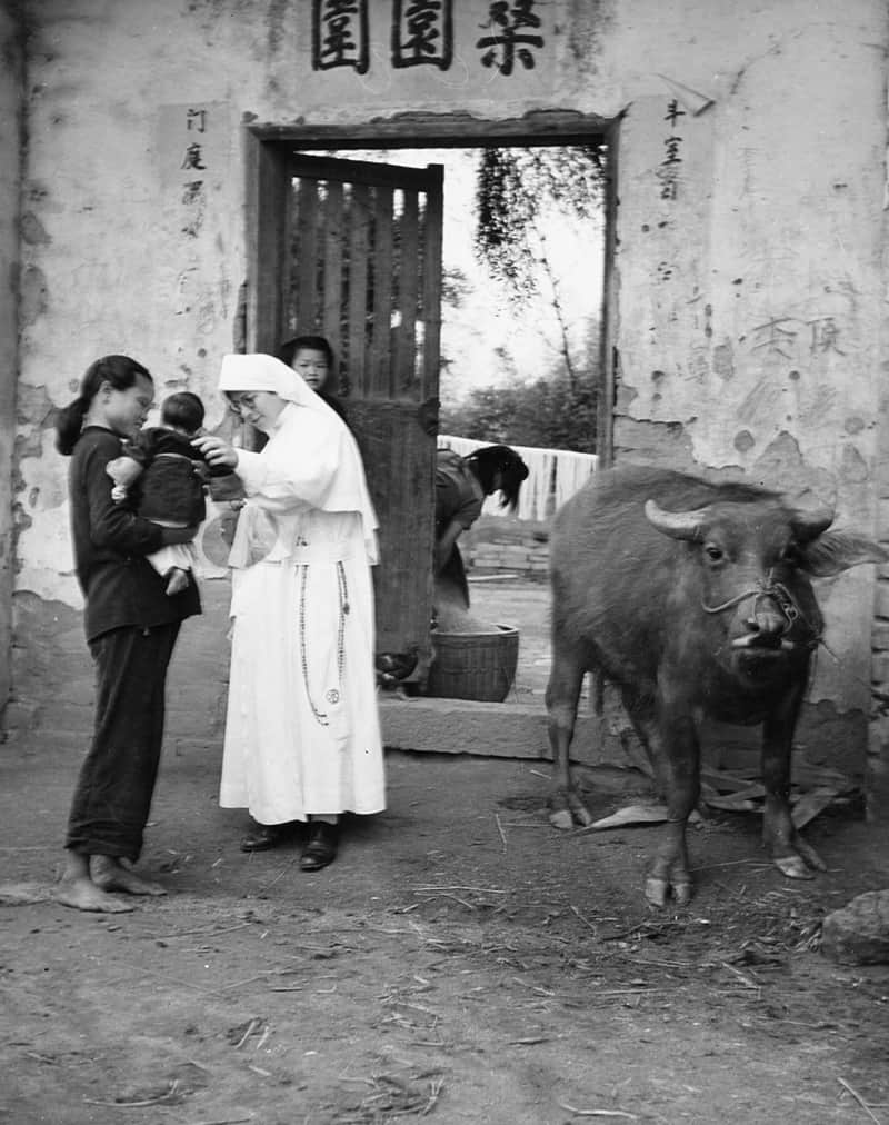 La Hermana Paulita Hoffmann, quien falleció en el 2019 después de haber servido como una misionera Maryknoll por 85 años, saluda a una madre y su bebé en Kaying donde profesó sus votos perpetuos en 1939.