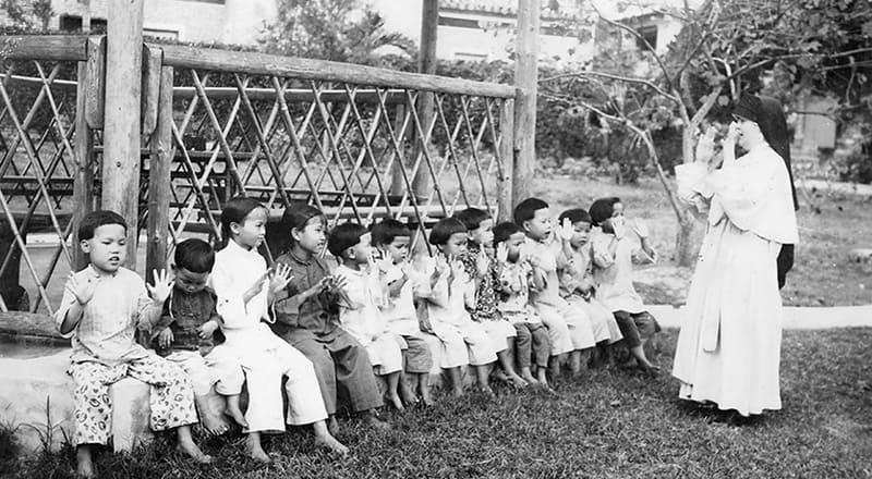 La Hermana M. Colombiere Bradley juega con niñas en un orfanato de Loting, China, uno de los muchos ministerios de las Hermanas Maryknoll en su primer destino misionero.