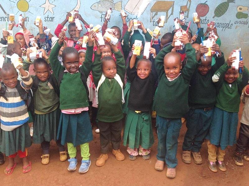 Los estudiantes de la Academia St. Paul, quienes no podían pagar uniformes y mochilas, recibieron estas necesidades escolares junto con bocadillos de parte del proyecto. (Cortesía de Samson Gladstone/Tanzania)