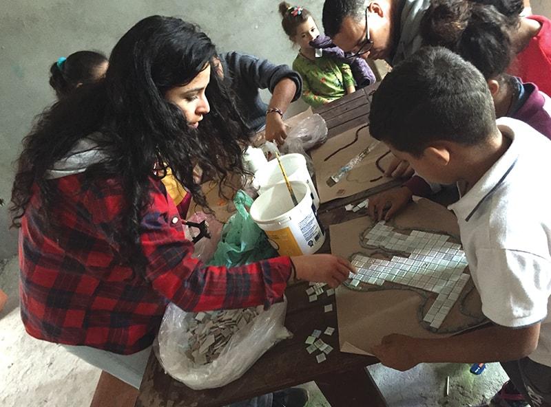 Margarita Durán ayuda a los niños a crear palomas que representan al Espíritu Santo para un mosaic en la Capilla de Nuestra Señora de Gracia en la comunidad de Haití.(Kathleen Maynard/Brasil)