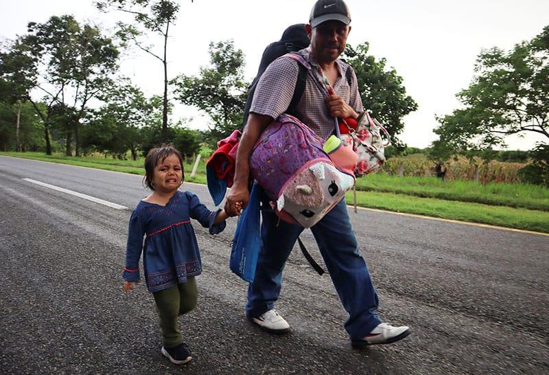 na niña y un hombre caminan en una caravana con otros de Centroamérica y el Caribe cerca de Escuintla, México, el 29 de agosto de 2021. Se dirigían a la Ciudad de México para solicitar asilo y estatus de refugiado. (Foto delCNS / José Torres, Reuters)